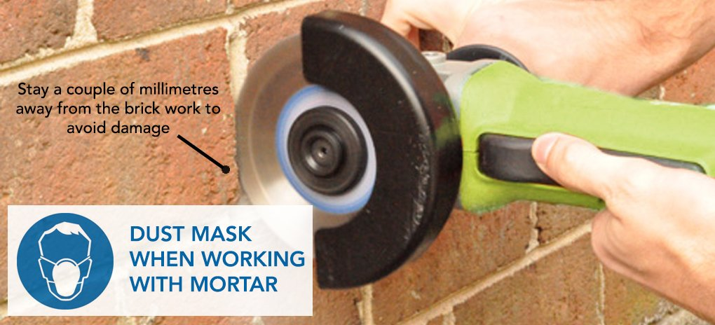 With your dust mask on, bring your grinder up to speed. Clear the joint by making two or three ~12mm cuts, all in the same direction, in the mortar. Stay a couple of millimetres away from the brick work to avoid the possibility of damage.